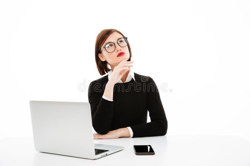 Concentrated som tänker den unga affärsdamen som använder bärbara datorn royaltyfri fotografi