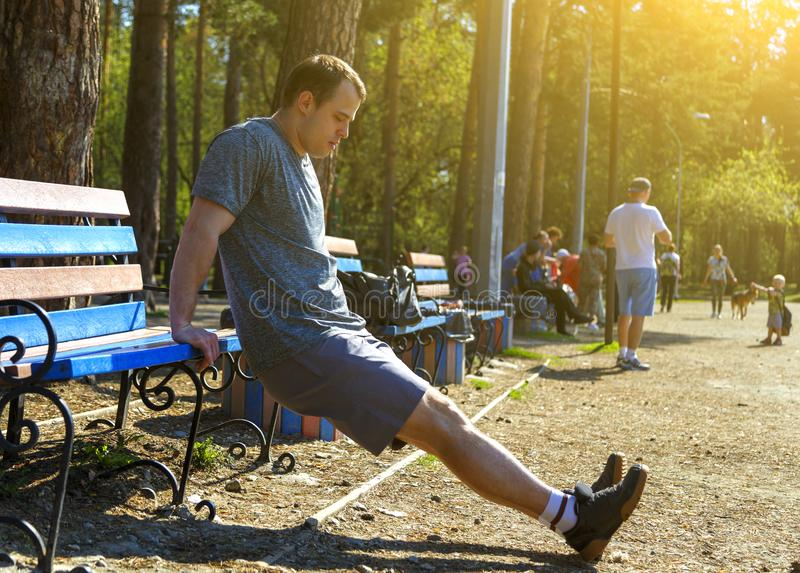 Sportsman doing reverse push-ups on bench in park. Concentrated sportsman wearing sport clothes doing reverse push-ups on bench in park. Male jogger exercising royalty free stock photo