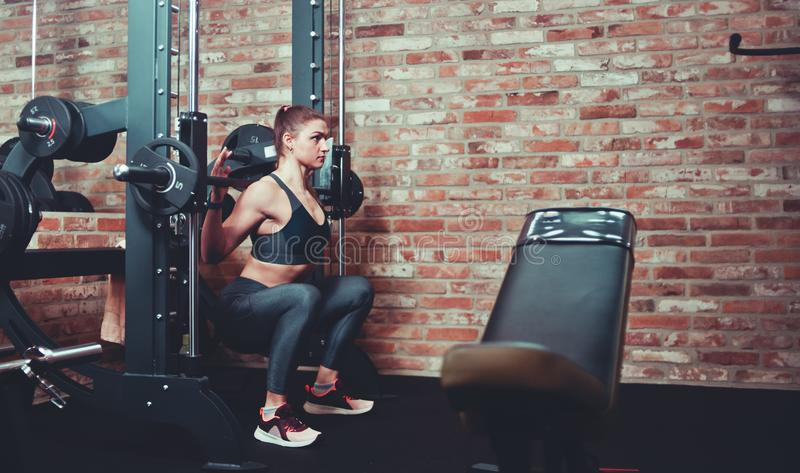 Concentrated sporty girl exercising squatting with barbell at  smith machine against brick wall in gym. Concentrated sporty girl exercising squatting with stock photo