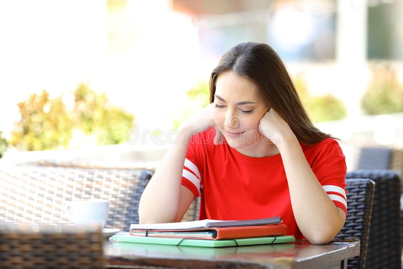 Concentrated student studying in a bar terrace. Concentrated student studying reading notes sitting in a bar terrace royalty free stock images