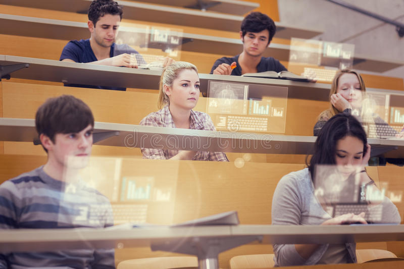Concentrated students in lecture hall working on their futuristic tablet. During lesson stock image
