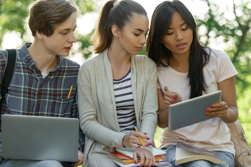 Concentrated students sitting and studying outdoors royalty free stock photos