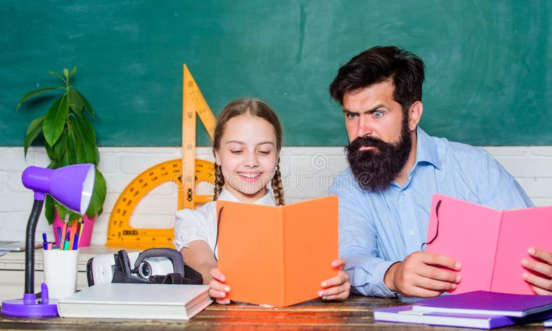 Concentrated on studying. small girl child with bearded teacher man in classroom. daughter study with father. Teachers royalty free stock photography