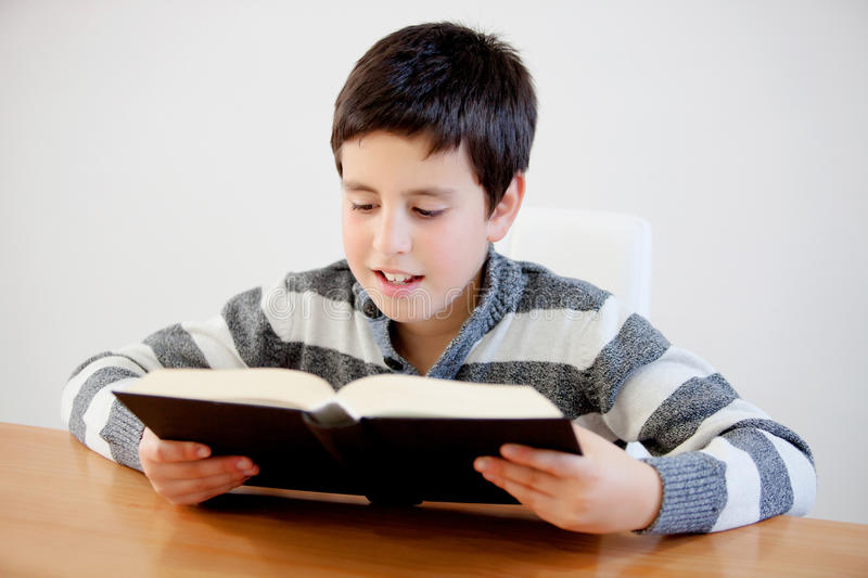 Concentrated teenage boy of thirteen reading a book stock photography