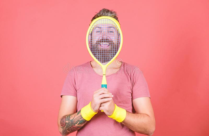 Concentrated on tennis court. Athlete hipster hold tennis racket in hand red background. Man bearded hipster wear sport royalty free stock photo