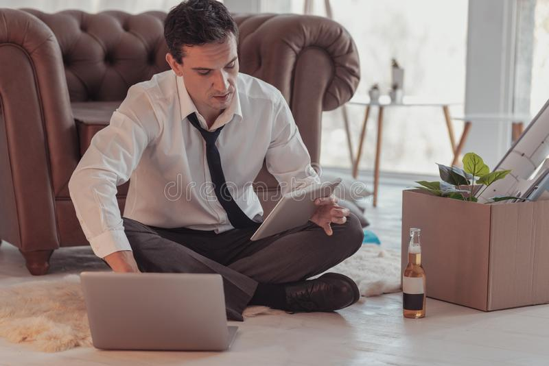 Concentrated tired freelancer working at home. Busy. Full length of young tired concentrated freelancer being formally clothed while sitting on the floor and royalty free stock photos