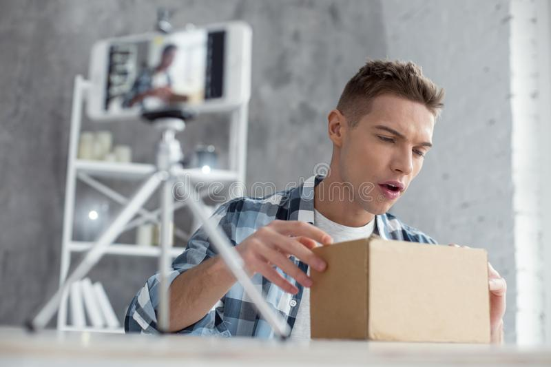 Concentrated vlogger opening his box stock photography