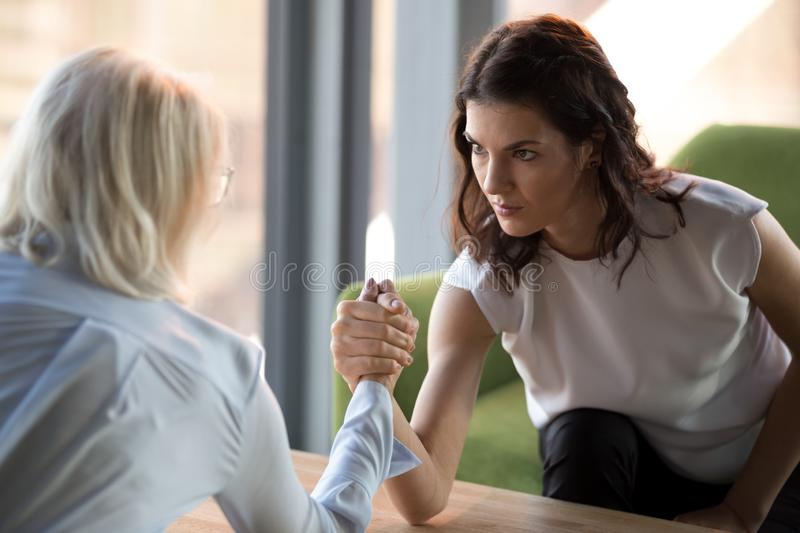 Concentrated woman arm wrestle with colleague demonstrating power. Side view of decisive concentrated millennial businesswoman arm wrestle with female competitor royalty free stock image