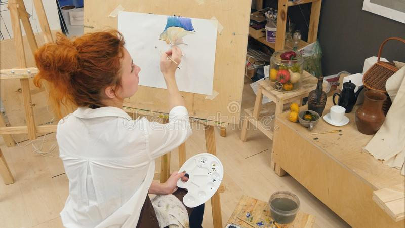 Concentrated woman artist painting pumpkin still life with watercolors royalty free stock images