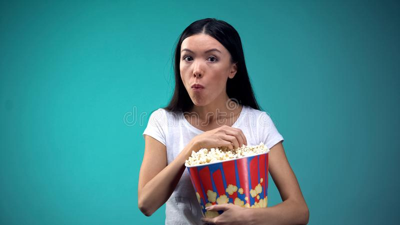Concentrated woman chewing popcorn and watching exciting film in cinema, concept. Stock photo royalty free stock image