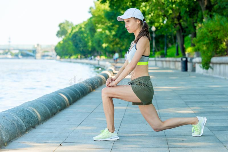 concentrated woman in sportswear with a muscular figure is warming up on a city embankment stock photography