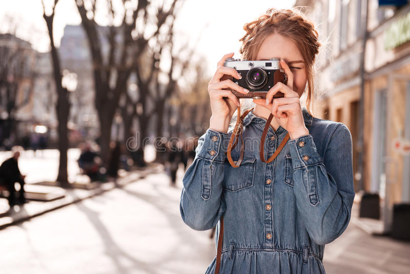 Concentrated woman taking pictures outdoors using old vintage camera stock images