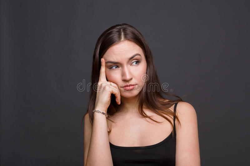 Concentrated woman thinking on gray background stock photos
