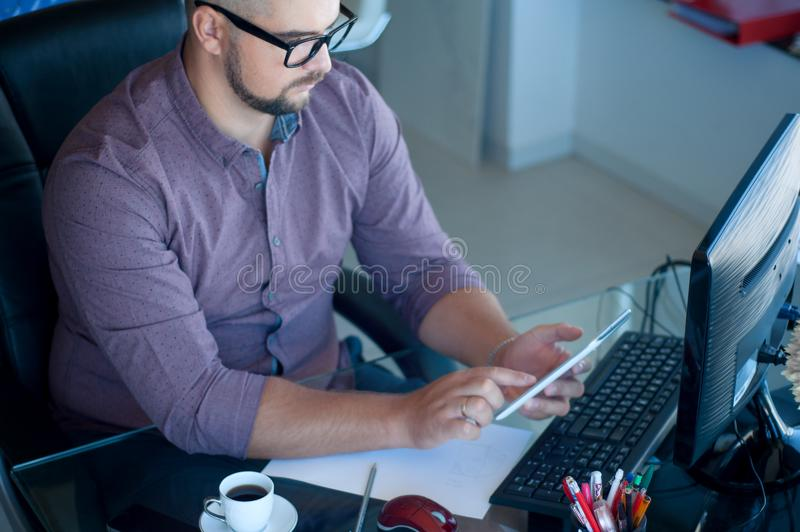 Concentrated on work. Concentrated young beard man working. Businessman sitting at his working place in office and writin y royalty free stock photography