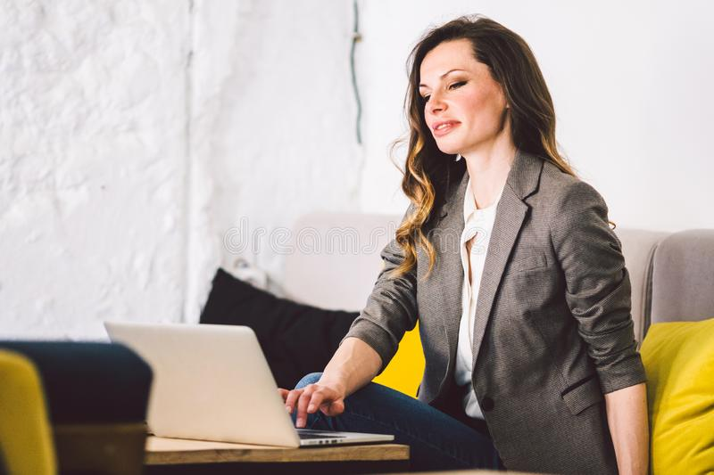 Concentrated at work. Confident young adult middle-aged woman in smart casual clothes, working on a laptop, sitting stock photo