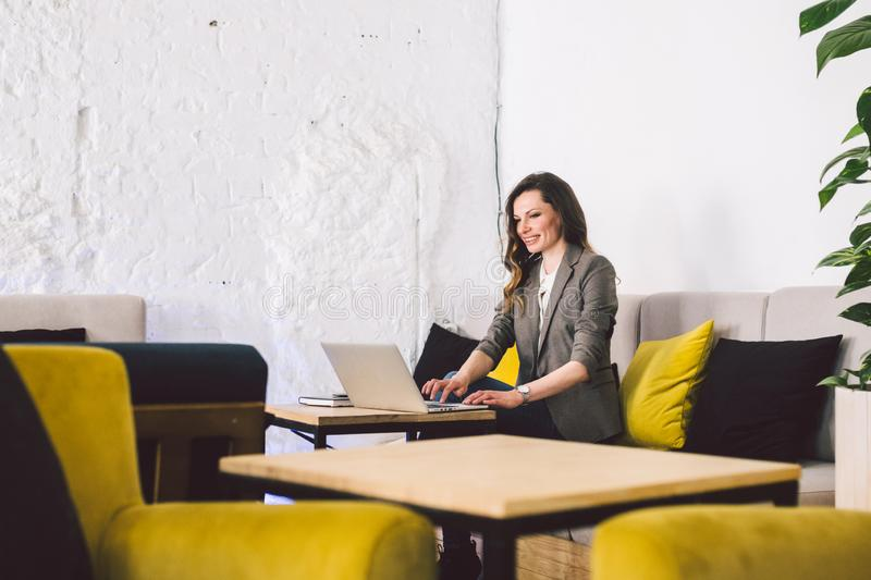 Concentrated at work. Confident young adult middle-aged woman in smart casual clothes, working on a laptop, sitting royalty free stock photos