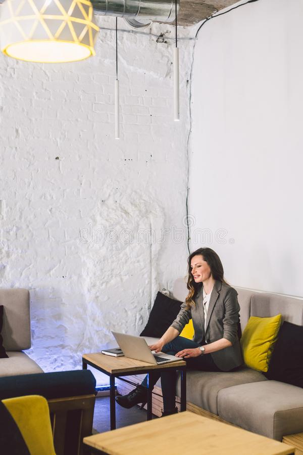 Concentrated at work. Confident young adult middle-aged woman in smart casual clothes, working on a laptop, sitting royalty free stock photography