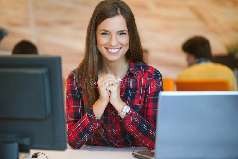 Concentrated at work. Young beautiful woman using her laptop while sitting in chair at her working place royalty free stock images