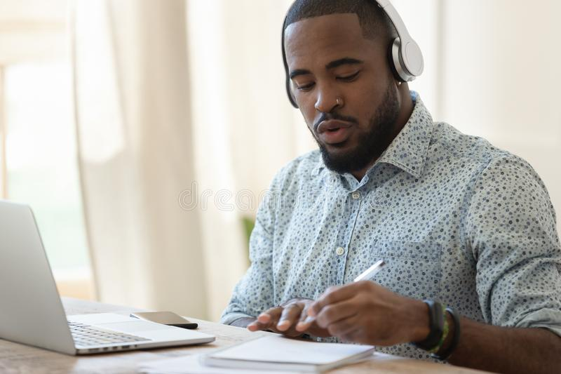 Focused black guy busy with certification training. stock image