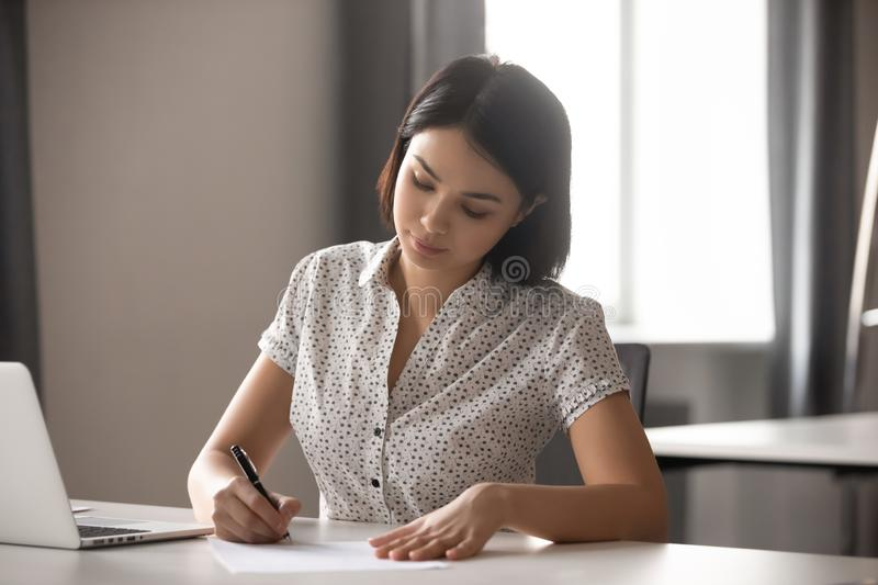 Concentrated young asian business woman signing important contract. Concentrated young asian business woman leader working with financial reports, signing stock images