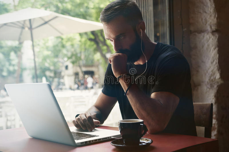 Concentrated Young Bearded Businessman Wearing Black Tshirt Working Laptop Urban Cafe.Man Sitting Wood Table Cup Coffee royalty free stock image