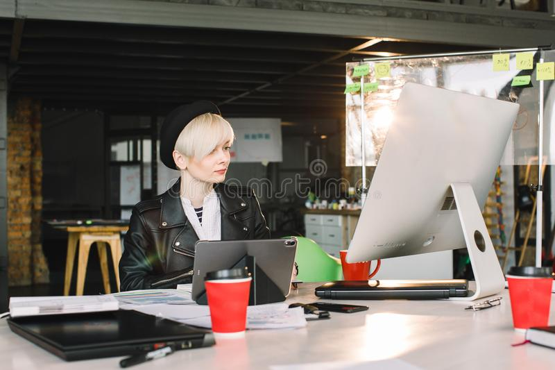 Concentrated young beautiful blond businesswoman in casual wear working on PC and tablet in bright loft modern office.  royalty free stock image
