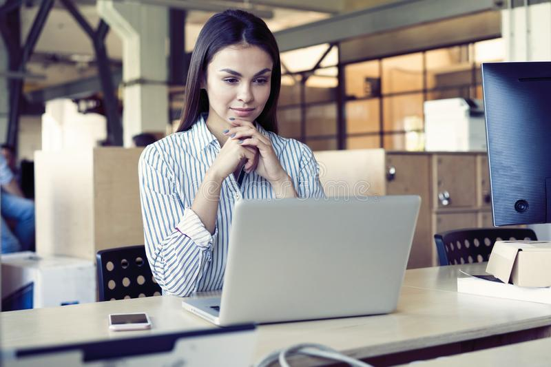 Concentrated young beautiful businesswoman working on laptop in bright modern office. stock photo
