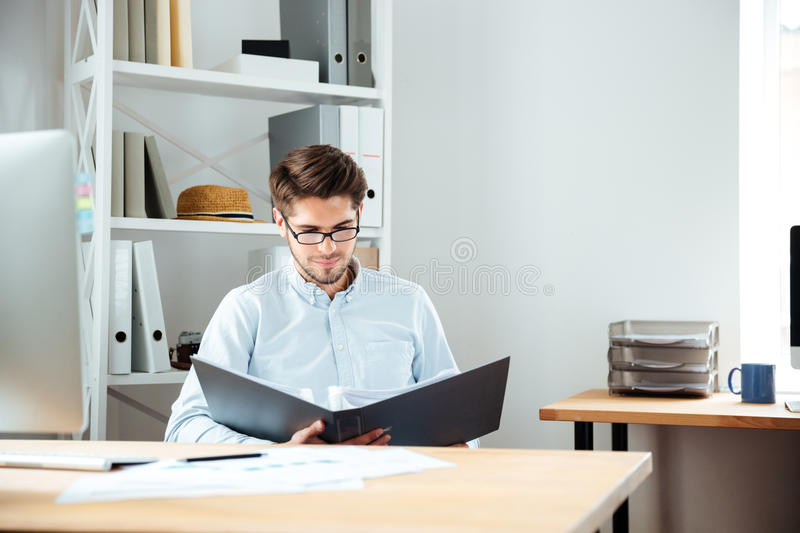 Concentrated young businessman working with documents in folder. At workplace royalty free stock images