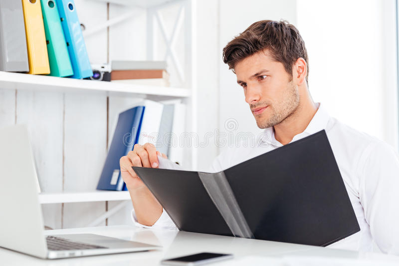 Concentrated young businessman working with documents in folder. At workplace stock images