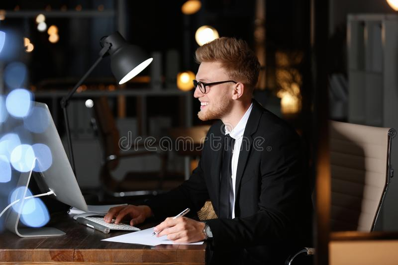 Concentrated young businessman working in office alone royalty free stock photo