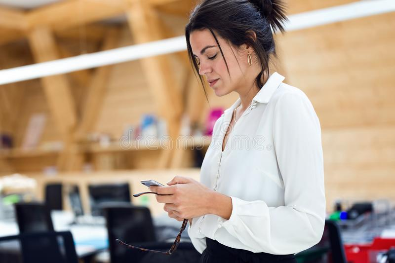 Concentrated young businesswoman texting with mobile phone on coworking place royalty free stock images