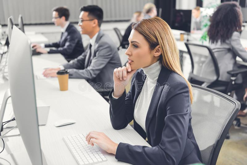 Concentrated young businesswoman using desktop computer while working with colleagues royalty free stock image