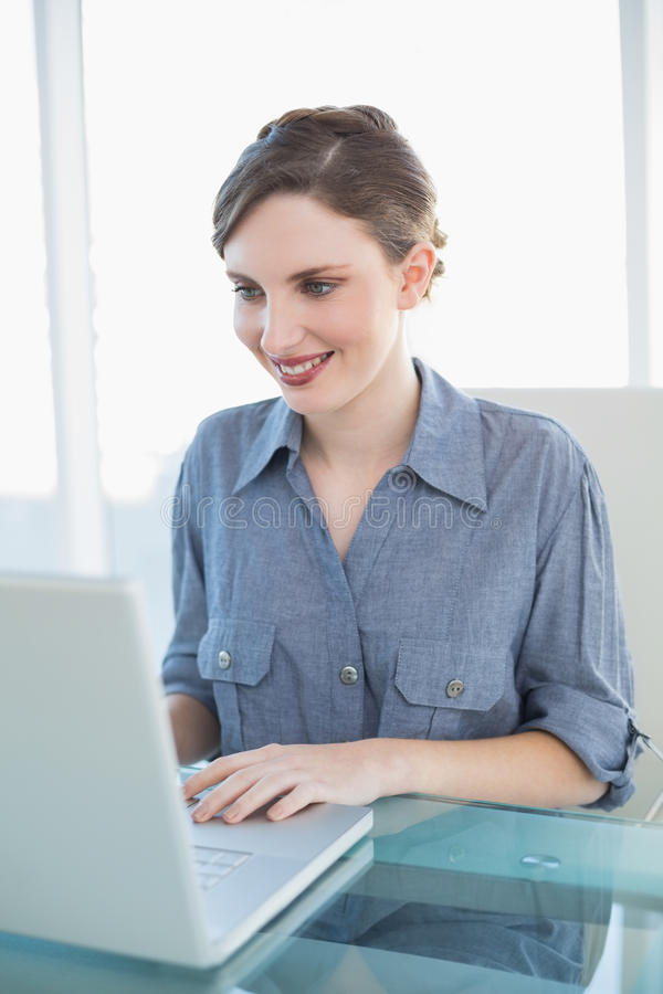 Concentrated young businesswoman working with her notebook sitting at her desk royalty free stock photos