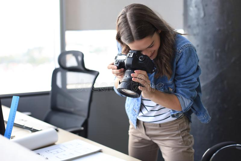 Concentrated young designer using digital camera while standing near the desk in her creative office stock images