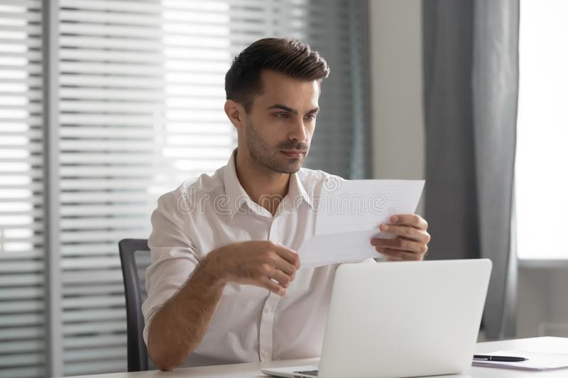 Concentrated young executive manager looking through financial documentation. stock images