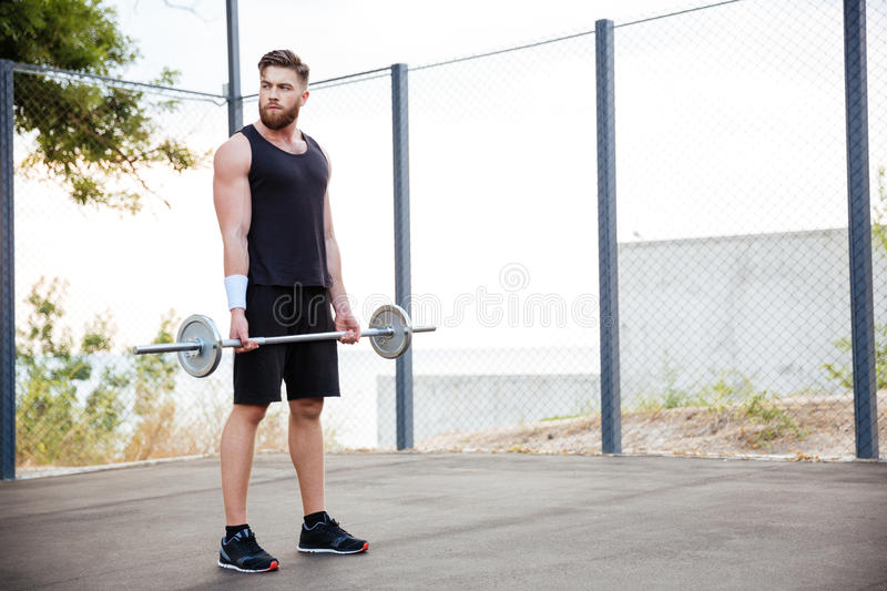Concentrated young man athlete working out with barbell royalty free stock photo