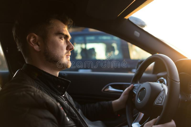 Concentrated young man driving a luxury car. Serious guy looking forward and holds hands on the wheel. Successful man in a hurry on business. Sun rays falling stock image