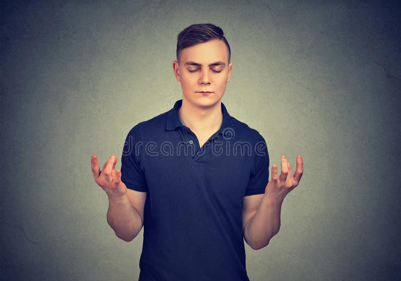 Meditating young man with eyes closed stock photo