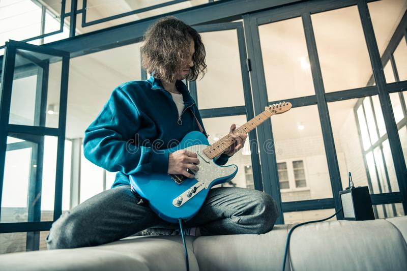 Concentrated young man lying on the back of grey sofa. Like a rock star. Concentrated young man lying on the back of grey sofa and showing his skill in music royalty free stock photography