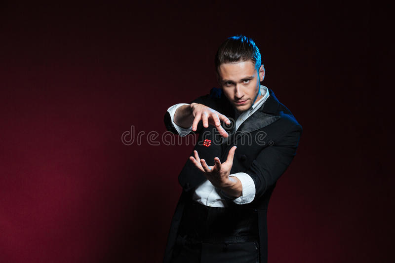 Concentrated young man magician conjuring tricks with red dice royalty free stock photos