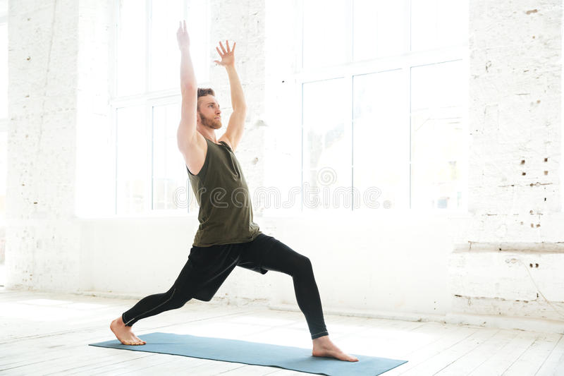 Concentrated young man parctising yoga pose on a fitness mat stock images