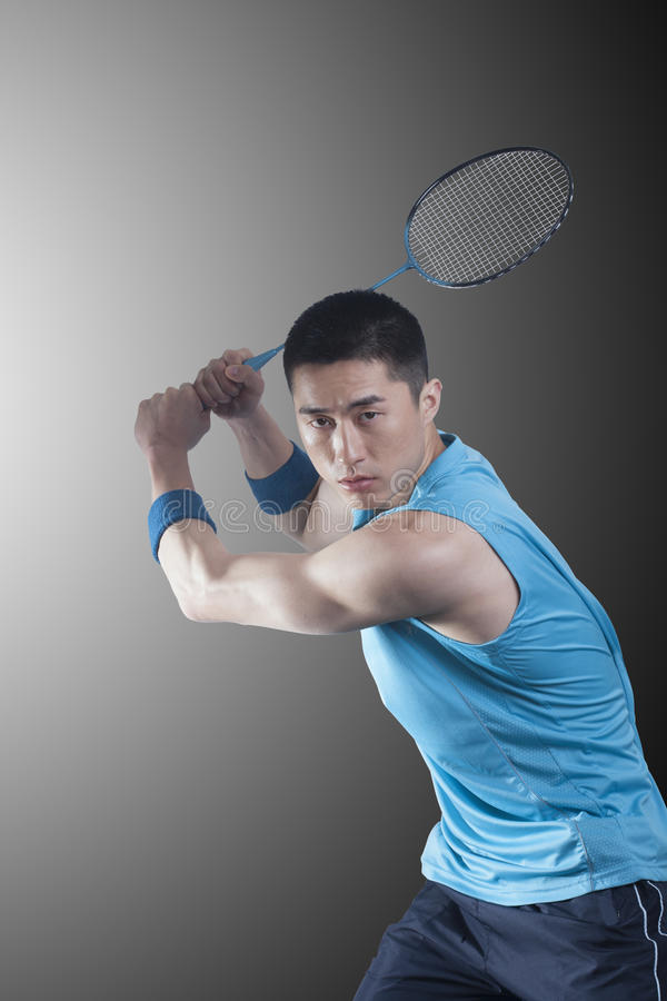 Concentrated Young man playing badminton, racket raised stock images