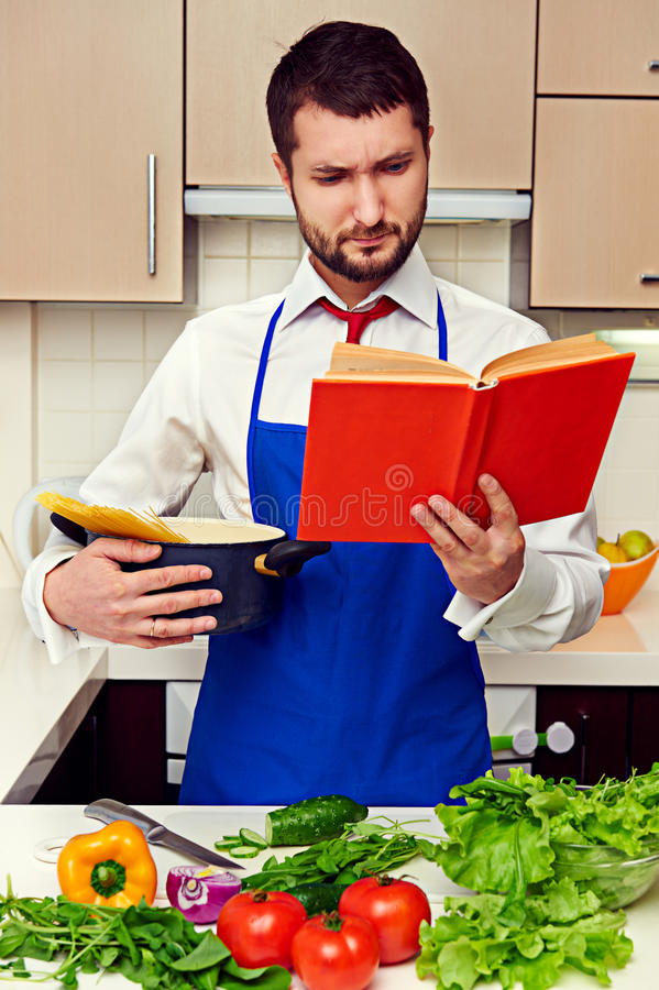 Concentrated young man reading cookbook stock photography