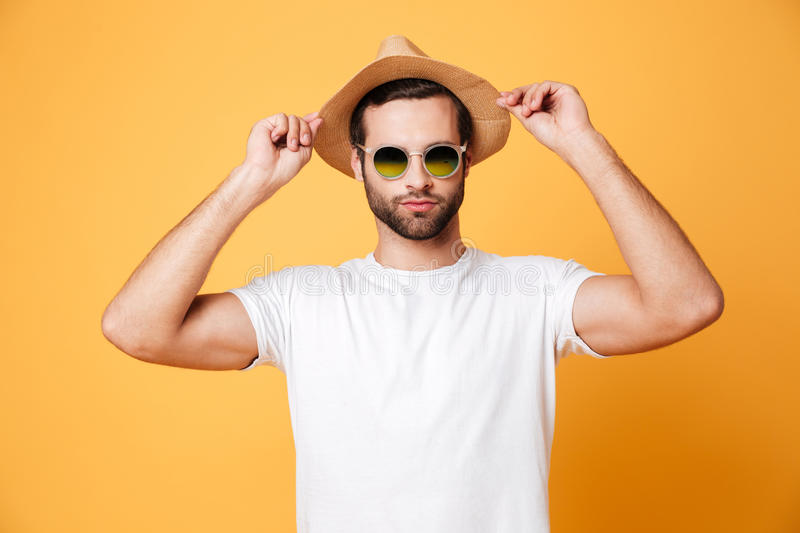 Concentrated young man standing isolated over yellow background stock images