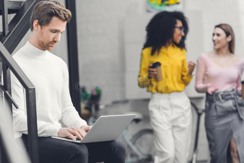 Concentrated young man using laptop and smiling female colleagues talking and walking behind stock image