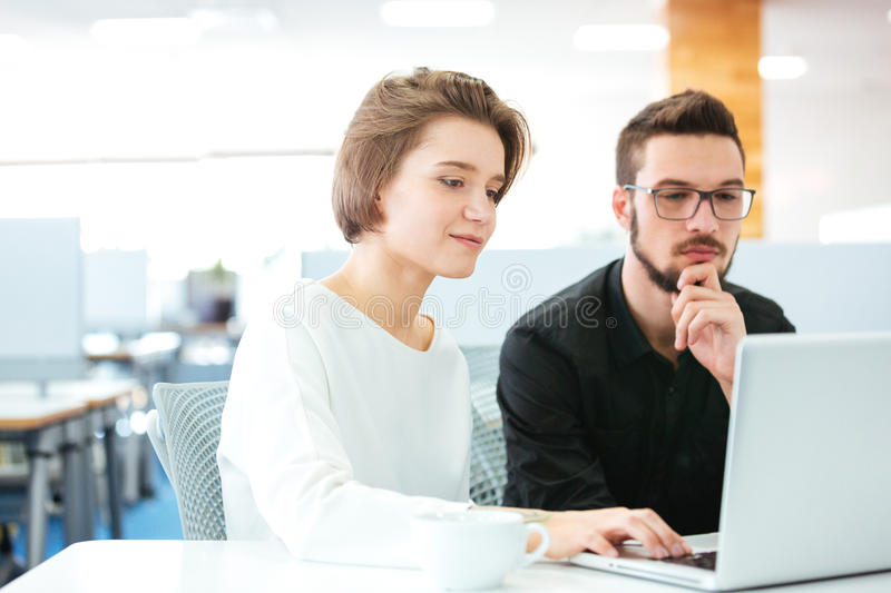 Concentrated young man and woman discussing new project using laptop stock photos