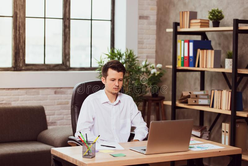Concentrated young manager man sitting at office desk working on laptop computer royalty free stock image