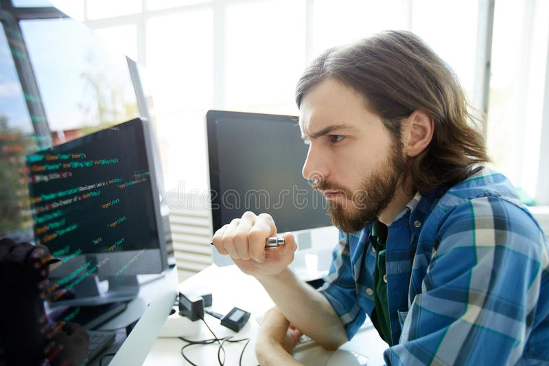 Programming specialist. Concentrated young software developer looking at data code on computer screen royalty free stock image