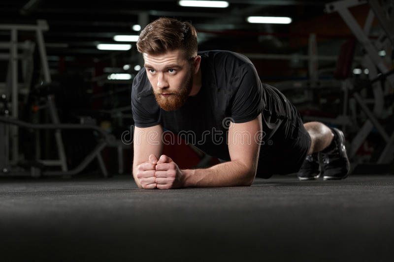 Concentrated young strong sports man make plank royalty free stock photos