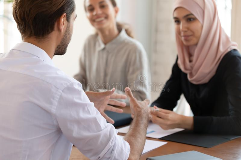 Concentrated young team leader explaining marketing strategy to multiracial colleagues. royalty free stock photo